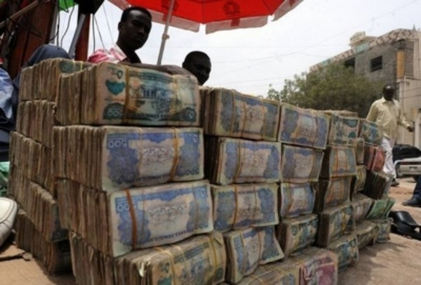 "A money changer talks on the phone next to piles of banknotes in Hargeisa in Somaliland. Local elections in the self-declared nation of Somaliland were ""largely peaceful and transparent"", international observers said Monday, but noted concern at ""weaknesses in safeguards against multiple voting."""