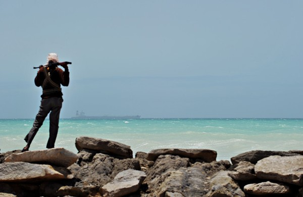 A pirate stands on the coast in Hobyo, Somalia.